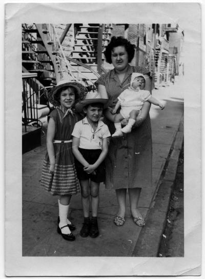 Une mère et ses trois enfants devant leur maison.