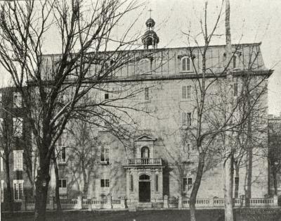 Photographie en noir et blanc représentant un édifice de cinq étages, avec un toit mansardé et un clocheton.