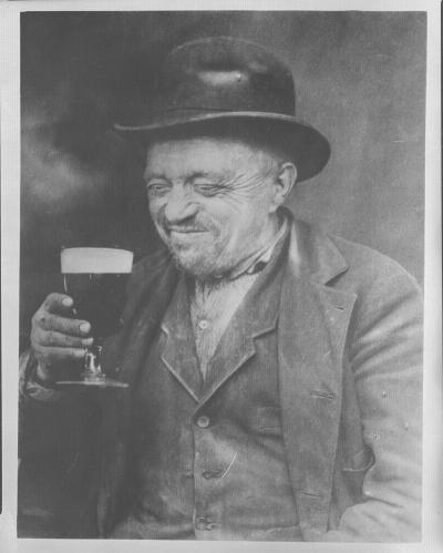 Vieil homme buvant une bière.