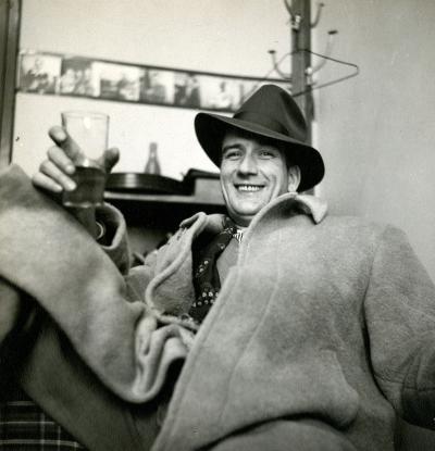 Un homme est assis. Il porte un manteau de drap et un chapeau de feutre, et a un verre à la main.