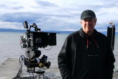 Denys Arcand avec sa caméra pose devant un cours d'eau
