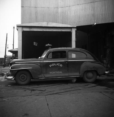 Photographie en noir et blanc d'une voiture du Service de police de Montréal.
