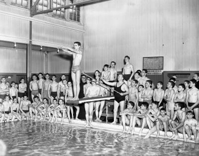 Groupe de jeunes hommes, du moniteur et de deux prêtres autour d'une piscine.