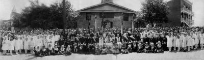 Les fidèles de la paroisse Saint-Michel se réunissent devant leur église pour souligner la venue de Mgr Nycétas Budka, premier évêque catholique ukrainien du Canada. À l'arrière des fidèles se trouve la petite église.