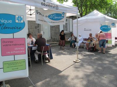 Photo montrant deux kiosques des cliniques de mémoires à l'extérieur et des gens qui viennent témoigner.
