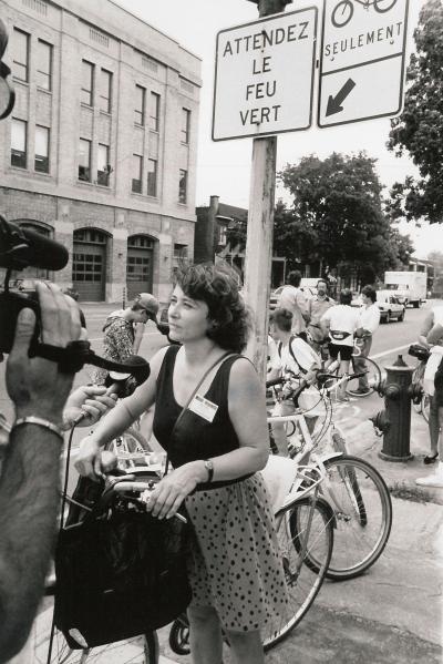 Claire Morissette s'adresse aux médias, à l'extérieur. Elle tient sa bicyclette.