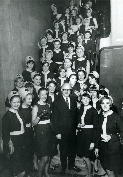 Jean Drapeau, le maire de Montréal reçoit les hôtesses du pavillon du Québec à l'hôtel de ville de Montréal pour les remercier et célébrer la fin de l'Expo 67. Monique Michaud se tient en haut à droite, vêtue de sa robe et de son chapeau d'uniforme, une s