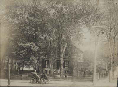 Photographie de la résidence clôturée et entourée d'arbres, ainsi que de la voiture en avant-plan.