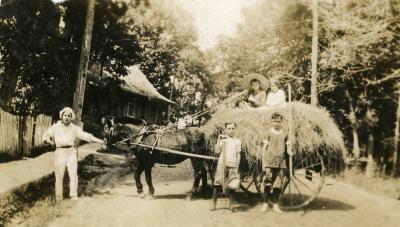 Un homme tenant un cheval qui tire une carriole de foin. Deux enfants posent devant et deux enfants sont assis sur le foin.