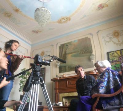 Un homme et une femme sont assis sur des chaises de bois. Devant eux, deux femmes les filment, debout derrière une caméra.