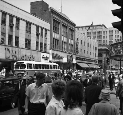 Vue sur les magasins de la rue Sainte-Catherine de jour, avec de nombreux passants et la circulation dans la rue.