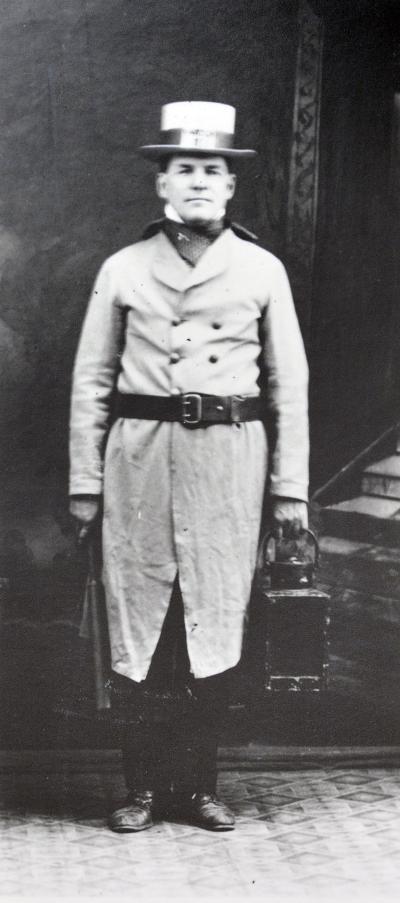 Image en noir et blanc d'un homme portant un chapeau et tenant une lanterne.