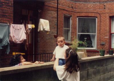 Une femme, de dos, tient son bébé qui est assis sur un muret dans la cour derrière le triplex familial. Une voisine le regarde.