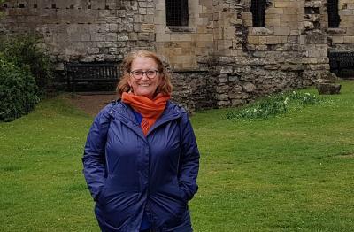 Photo couleur d'une femme souriante en plan rapproché, prise à l'extérieur.