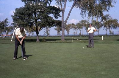 Photographie couleur de deux hommes jouant au golf.