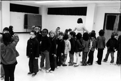 Quinze élèves se tiennent debout, en file. En arrière plan, une enseignante et des élèves.