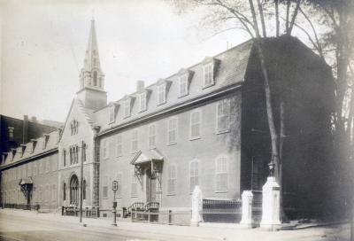 Immeuble ancien, de trois étages, avec clocher, bordant une rue.