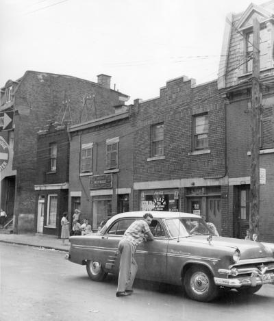 Deux jeunes hommes sont accoudés à une voiture stationnée devant une rangée de maisons à deux et trois étages dans la rue de l'Hôtel-de-Ville.