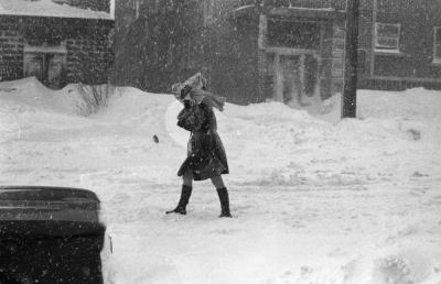 Une jeune femme tente de se protéger du vent et de la neige coiffée d'un journal