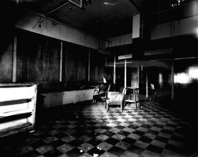 Intérieur d'une pièce sombre au plancher carrelé où il n'y a que quelques meubles.