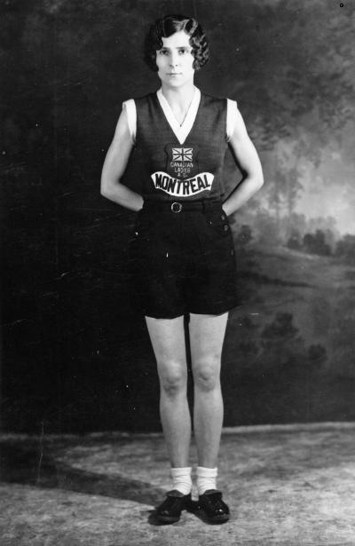 Portrait d'une femme debout portant un chandail sans manche sur lequel on lit Canadian Ladies A. O. Montreal