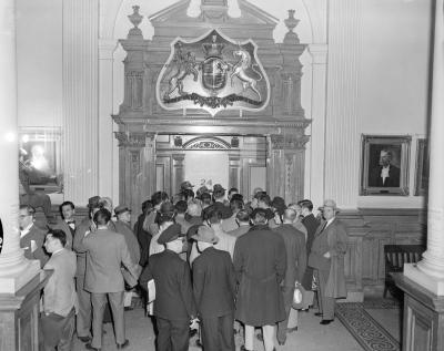 Une foule d'hommes se tient devant une porte ouvragée. Juste au-dessus des têtes, le nombre « 24 » est visible.