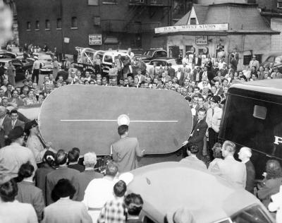 Photographie en noir et blanc d'une foule se tenant à l'extérieur et regardant des policiers embarquer une table à jouer dans un fourgon.