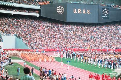 Photographie couleur de la délégation soviétique en orange paradant sur la piste du stade.