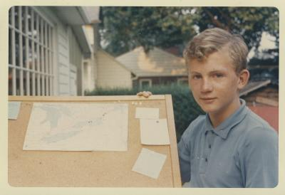 Garçon de 13 ans posant avec un tableau de liège avec une carte et autres cartons épinglés