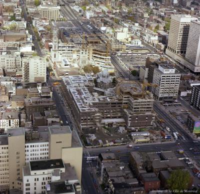Photographie aérienne couleur du centre-ville avec le chantier de construction de l'université au centre, entourant les églises.