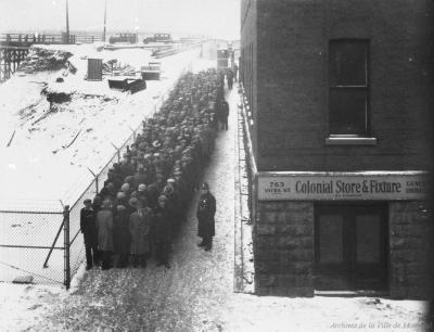 Photographie d'une file de chômeurs en attente près de l'entrée du refuge, sous la supervision de trois policiers.