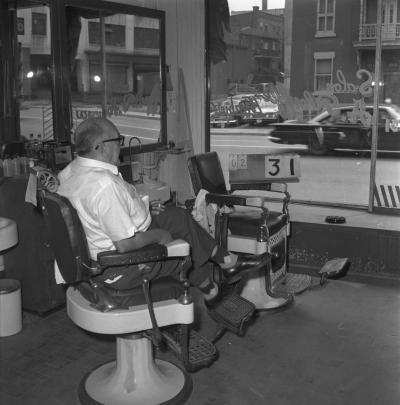Un homme est assis à l'intérieur du salon de coiffure Barbier A. Plouffe et regarde à l'extérieur par la grande fenêtre.