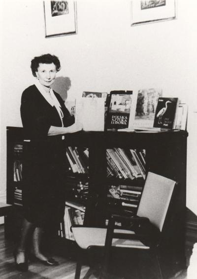 Wanda Stachiewicz tenant un livre, une bibliothèque derrière elle