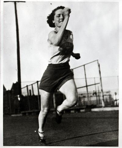 Une coureuse pose en position de départ un genou posé au sol.