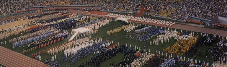 Cérémonie d'ouverture des Jeux olympiques. On voit le Stade sans toit, rempli d'athlètes et de spectateurs.