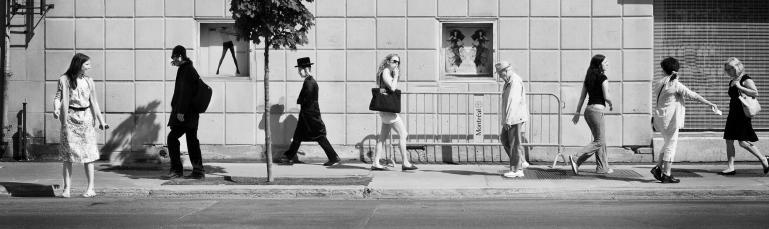 Photo en noir et blanc montrant une scène de rue : huit personnes circulent sur un trottoir du Mile End