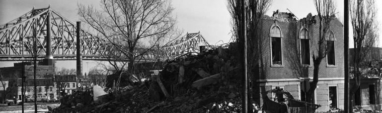 Bâtiment démoli dans le quadrilatère de Radio-Canada, avec le pont Jacques-Cartier en arrière-plan, 1963.