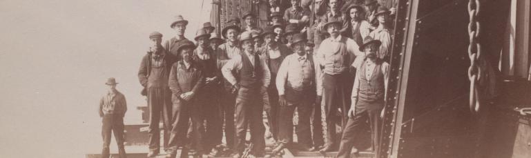 Les hommes qui ont travaillé à la construction du pont posent devant et sur la structure métallique du pont.