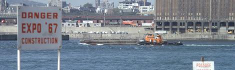 """Vue montrant à l'avant-plan l'île Sainte-Hélène  avec un panneau disant """"Danger Expo 67 Construction"""", avec Montréal à l'arrière-plan."""