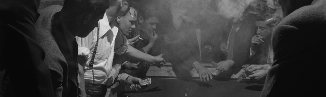 Photo noir et blanc montrant des hommes jouant aux cartes dans une salle enfumée.