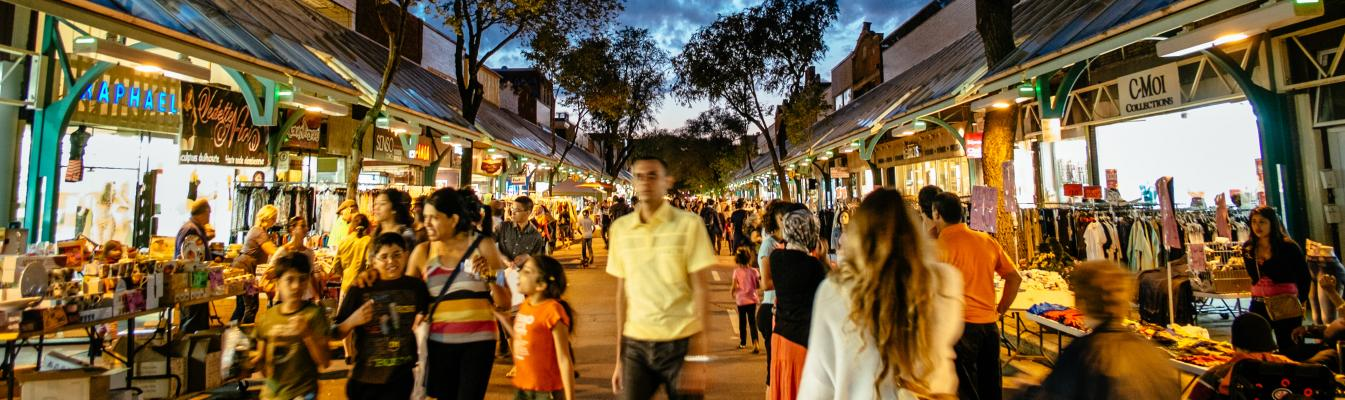 Scène de rue en soirée avec la vente-trottoir de la Plaza St-Hubert qui est en cours, les gens se promènent et magasinent.