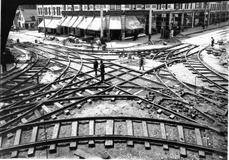 Photographie en plongée d'un croisement de voies de tramway à l'angle de deux rues.
