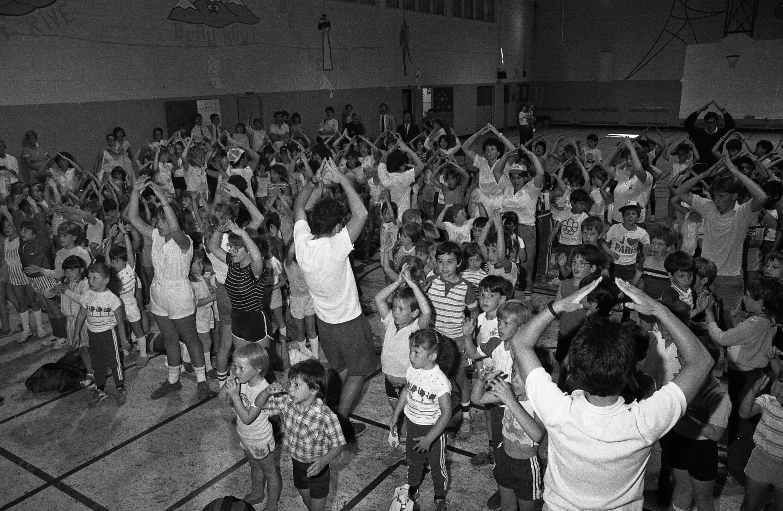 Une foule d'enfants suit les mouvements d'un moniteur dans un gymnase.