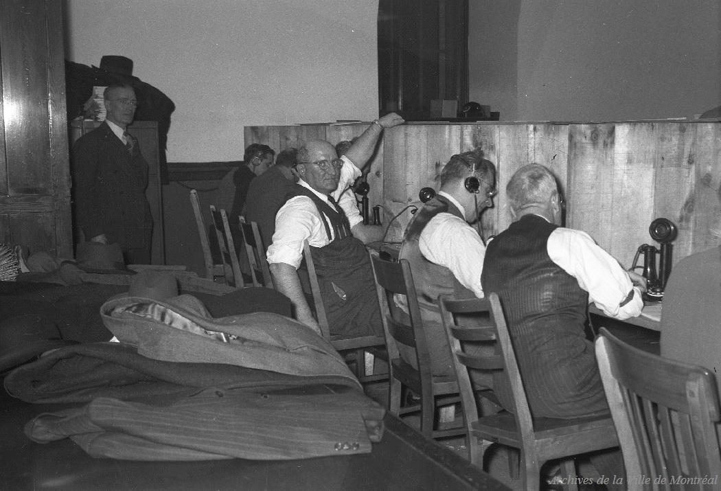 Photographie des employés préposés à la réception des appels des résultats du vote dans une salle aménagée pour les élections.