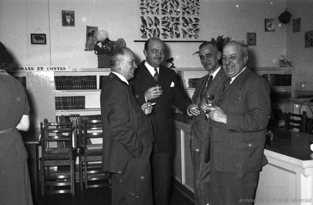 Quatre hommes verre à la main sourient dans une bibliothèque.