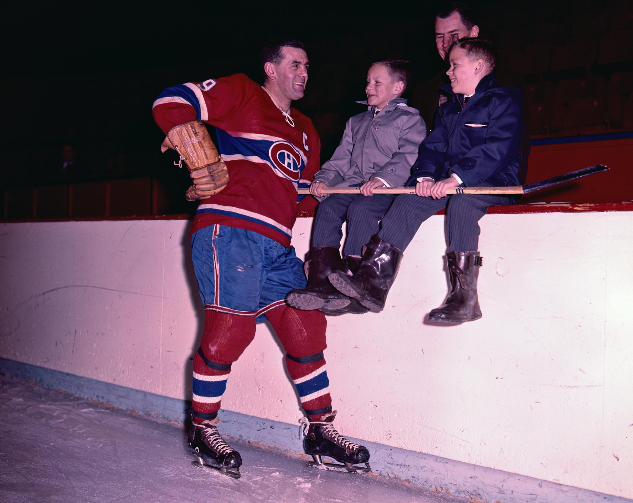 Photographie couleur de Maurice Richard affublé de son équipement du Canadien, souriant à deux jeunes garçons tenant un bâton de hockey.