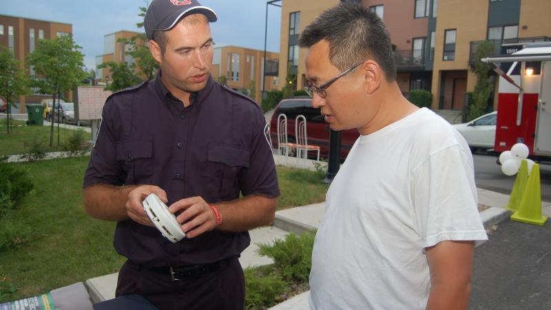 Fire safety educator with Montréal resident during a public awareness activity