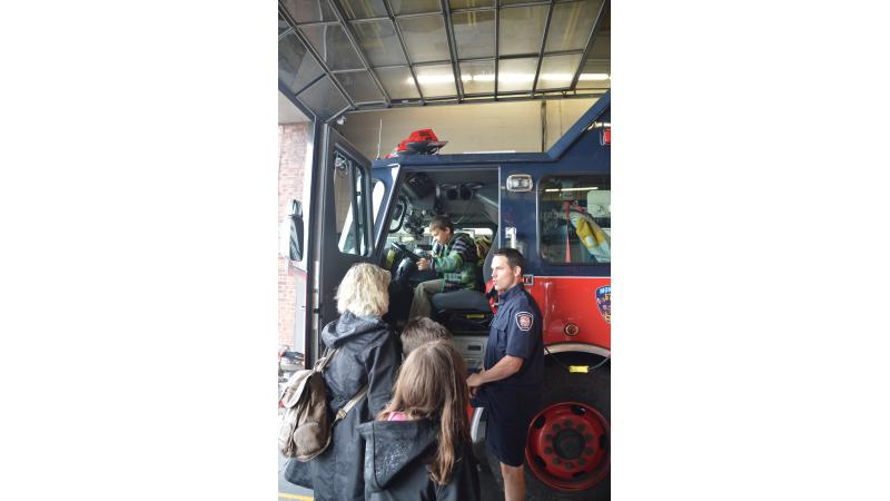 Residents chat with a firefighter on a visit to the fire station