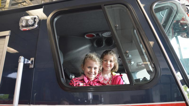 Two children in a fire safety vehicle on a visit to the fire station