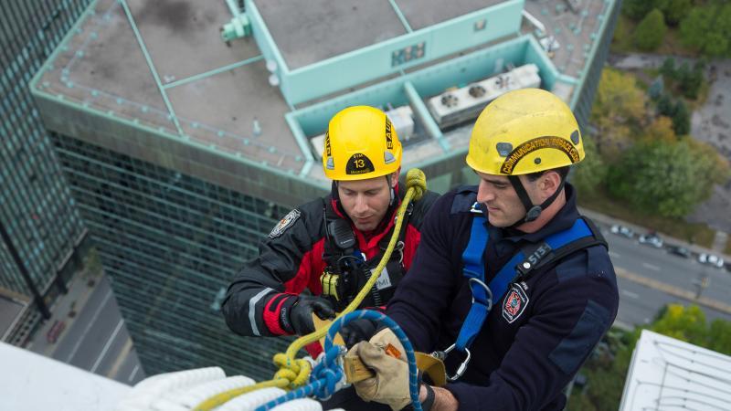 Deux pompiers au sommet d'un édifice lors d'une simulation de sauvetage en hauteur.